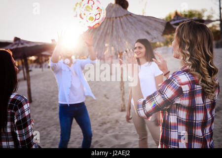 Group of happy young people enjoying summer vacation on beach - Stock Photo