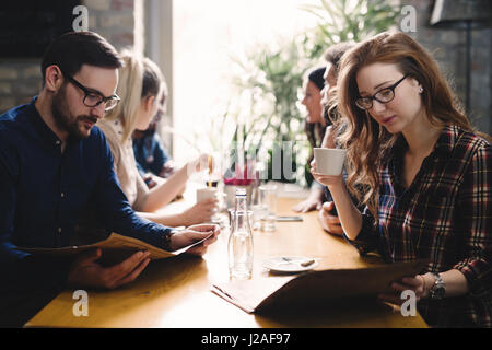 Group of happy business people eating together in restaurant - Stock Photo