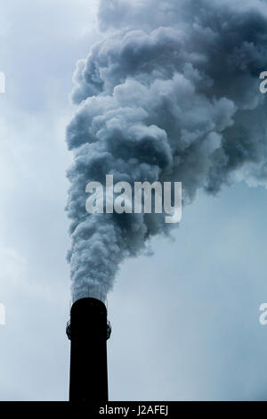 China, Chongqing, Steam and smoke billows from smokestacks at massive coal-fired power plants on cloudy autumn afternoon - Stock Photo
