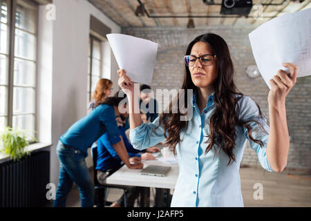 Overworked stressful businesswoman overwhelmed with papers in office - Stock Photo