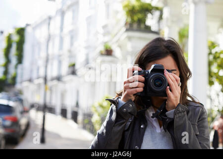 Young woman in street taking photo with SLR camera, close up - Stock Photo
