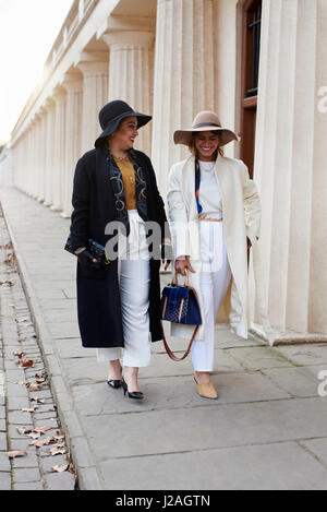 LONDON - FEBRUARY, 2017: Full length view of two fashionable women wearing coats and hats walking in street, London - Stock Photo