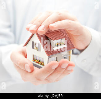 House protection. Small toy house in hands - Stock Photo