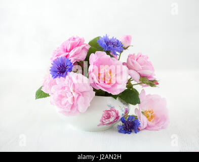 Colorful bouquet of light pink roses and cornflowers on pale  grey  background. - Stock Photo