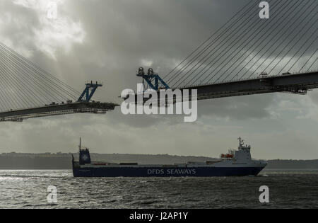 Container ferry passing Queensferry Crossing under construction, North Queensferry, Scotland, United Kingdom - Stock Photo