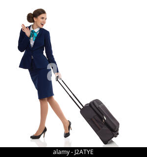 Smiling woman in blue suit and skirt is walking with trolley bag, looking back over shoulder and waving. Side view. - Stock Photo
