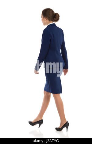 Young woman in blue suit, skirt and black high heels walking. Rear side view. Full length studio shot isolated on - Stock Photo