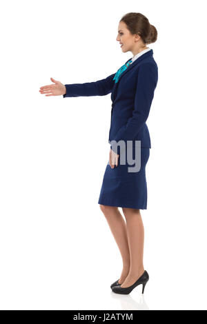Young woman in blue formalwear and high heels is standing and giving hand for a handshake. Side view. Full length - Stock Photo