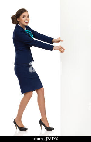Young woman in blue formalwear and high heels is pulling white banner and looking at camera. Side view. Full length - Stock Photo