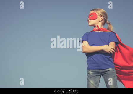 Happy little child playing superhero. Kid having fun outdoors. Concept of girl power. - Stock Photo