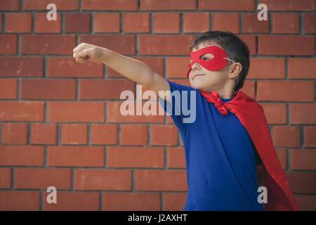Happy little child playing superhero. Kid having fun outdoors. Concept of boy power. - Stock Photo