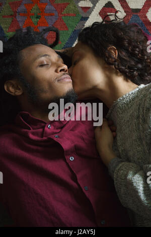 Directly above shot of woman kissing man while lying on carpet - Stock Photo
