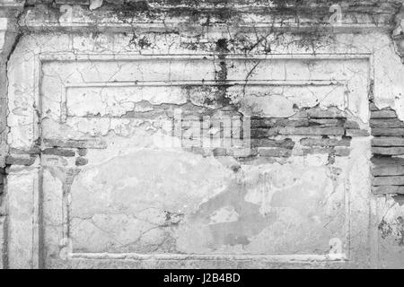Broken, old and dirty plastered wall revealing old brick wall in black&white. - Stock Photo