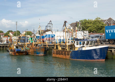 Row of working fishing boats in Camber docks in old Portsmouth. Lots of detail showing the fishing rigs and nets. - Stock Photo