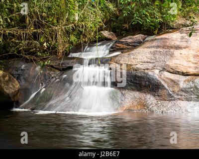 Small waterfall in between trees, in Joatinga park,near Paraty, Rio de Janeiro, Brazil. - Stock Photo