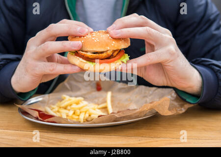 close up view of man's hands with american burger. - Stock Photo