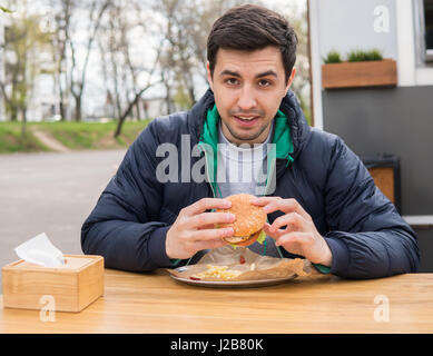 A portrait of young man eating a burger in street food cafe - Stock Photo
