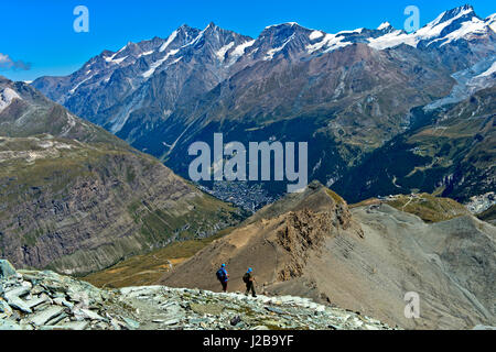 Hikers descending on the trail from the Hoernlihuette back to Zermatt, Valais, Switzerland - Stock Photo