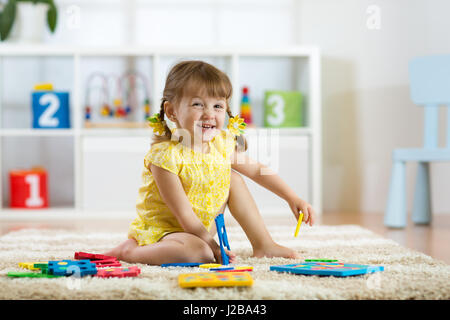 Child girl playing indoors with sorter toy sitting on soft carpet - Stock Photo