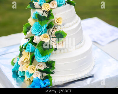 Beautiful wedding cake with blue and yellow roses - Stock Photo