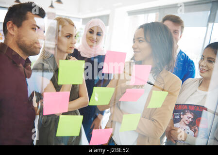 Business people looking at adhesive notes - Stock Photo