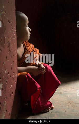 Myanmar, Yangon. A young boy monk sits in the doorway of a monastery. - Stock Photo