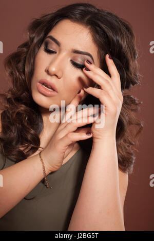 beautiful girl hairstyle curls on a brown background