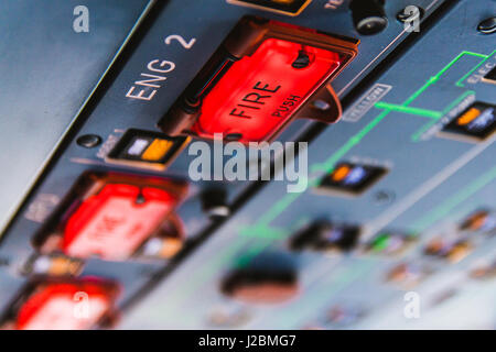 Fire pushbuttons and warning lights on the overhead panel in an Airbus A320 cockpit. Bright red warning lights come - Stock Photo