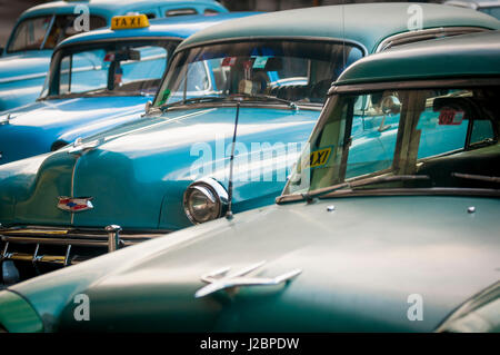 HAVANA - JUNE, 2011: Vintage American cars serving as active taxis stand parked in a row in a street in Centro. - Stock Photo