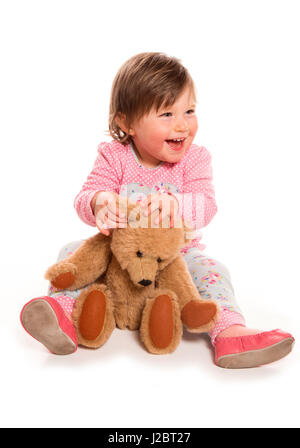toddler getting ready for bed in pyjamas with teddy cutout - Stock Photo