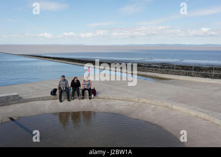 A family of three sit on the edge of a saltwater pool at Clevedon, on 22nd April 2017, in North Somerset, England. - Stock Photo