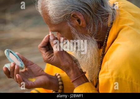 Sadhu making religious markings to face at Kumbh Mela festival - Stock Photo