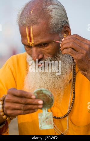 Sadhu making religious markings to face at Kumbh Mela festival, India - Stock Photo
