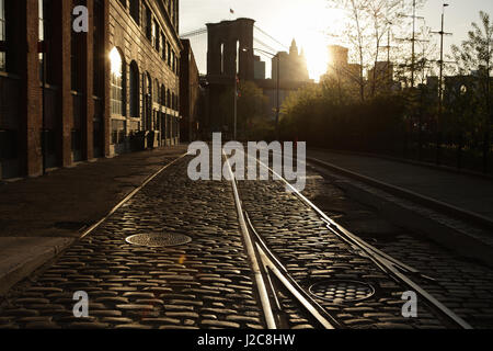 Old backstreet in DUMBO Brooklyn, New York at sunset with the Brooklyn Bridge down Water Street. - Stock Photo