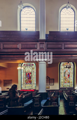 Beautiful stained glass windows and benches of St Anns Church in Manchester, UK