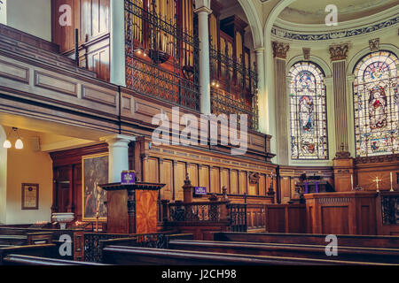 Saint Annes Church in Manchester, UK. Side view of benches, organ and beautiful mosaic windows