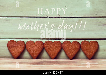 the text happy mothers day and of some heart-shaped cookies in line against a pale green rustic wooden background - Stock Photo
