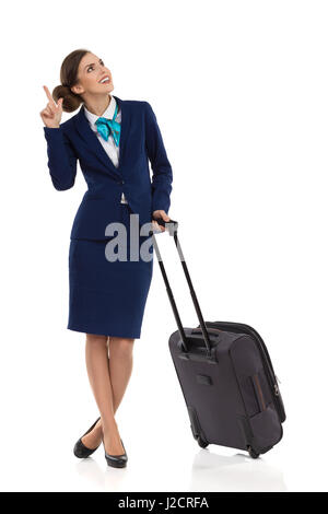 Smiling woman in formal blue suit and skirt standing with trolley bag, looking up and pointing. Full length studio - Stock Photo