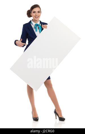 Young woman in blue formalwear and high heels, holding blank placard, pointing and smiling. Front view. Full length - Stock Photo