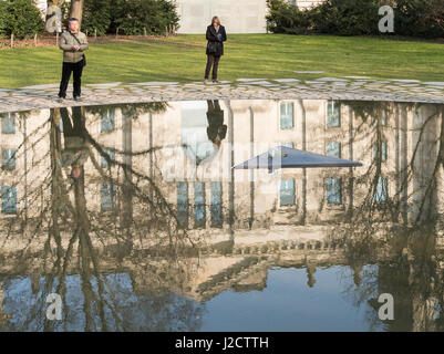 Germany, Berlin. Tourists at Holocaust Memorial reflecting pool. Credit as: Wendy Kaveney / Jaynes Gallery / DanitaDelimont.com - Stock Photo