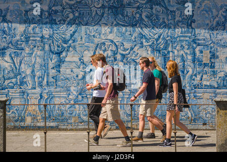 Porto Portugal azulejos, a group of young people walk past a wall in the Se cathedral cloisters decorated with blue - Stock Photo