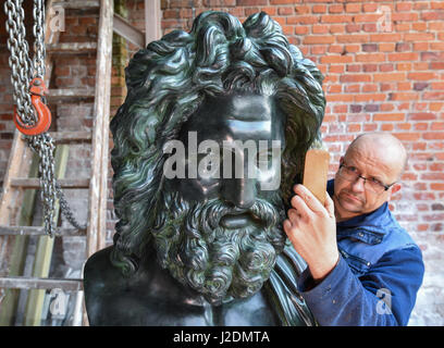 Wegendorf, Germany. 28th Apr, 2017. Foundry worker Ernest Pusch applies conservation wax to a sculpture of the Roman - Stock Photo