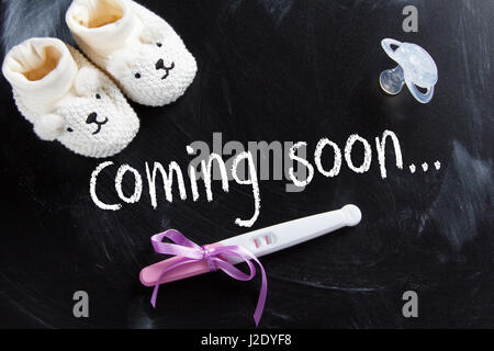 Waiting for labour. 'Coming soon' inscription on black chalkboard with positive pregnancy test. - Stock Photo