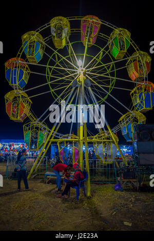 BANYUWANGI, INDONESIA: Locals seen playing around in front of small ferris wheel, located inside charming park area, - Stock Photo