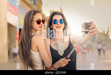 2 young women in the city taking a selfie - Stock Photo