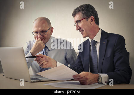 2 businessmen discussing and looking at tablet - Stock Photo