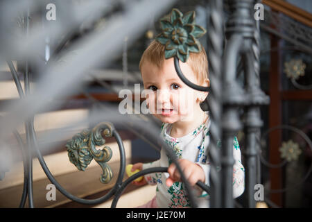 little girl smiling and looking through a metal fence - Stock Photo