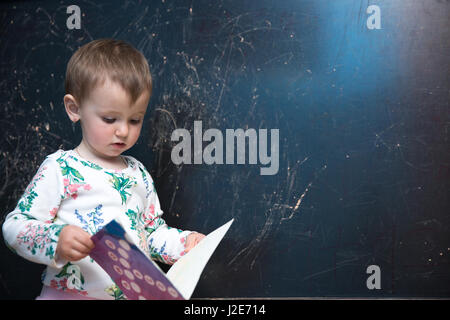 Beautiful little girl holding a book - Stock Photo