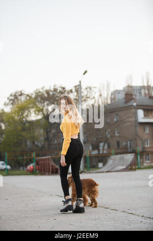 Beautiful blonde looking like Jennifer Aniston is standing with dog against backdrop of urban homes - Stock Photo