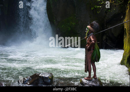Colorfully dressed and painted local tribal chief stands before a waterfall in the Highlands of Papua New Guinea, - Stock Photo